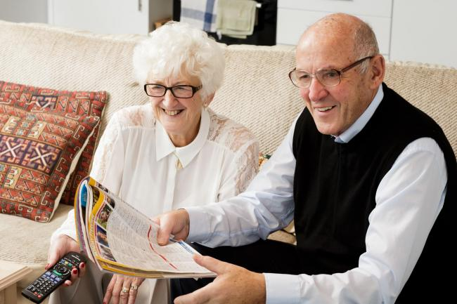 An elderly couple watching television.