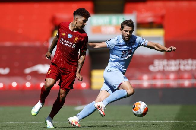 Liverpool's Roberto Firmino (left) and Burnley's James Tarkowski battle for the ball during the Premier League match at Anfield Stadium, Liverpool.