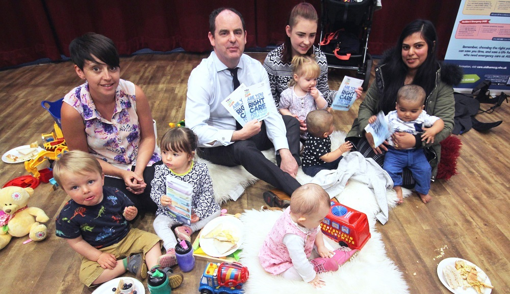 : Dr John Patterson, Chief Medical Officer for the NHS Oldham CCG, highlights the new campaign with parents and children at Oldham Library