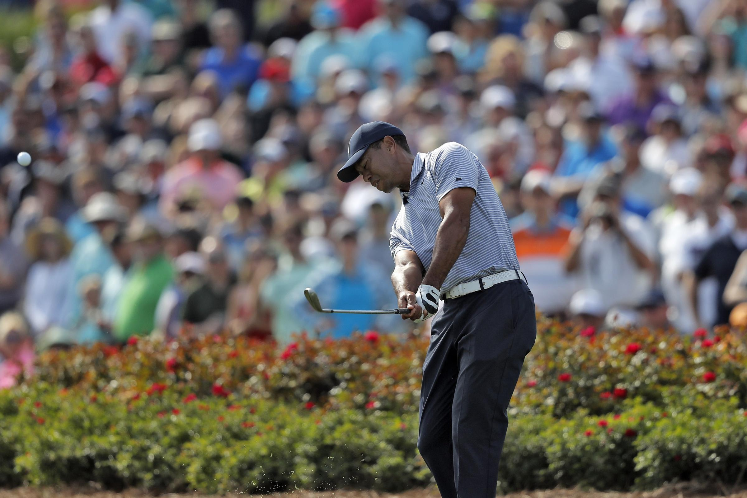 Tiger Woods plays a shot from the drop zone after hitting his tee shot into the water on the 17th hole